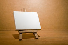 Blank canvas easel. A mini blank artists' canvas on a mini wooden easel Royalty Free Stock Image