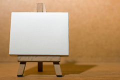 Blank canvas easel. A mini blank artists' canvas on a mini wooden easel Royalty Free Stock Images