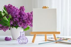 Blank canvas on easel, watercolor paints, brush for painting and lilac flowers on table. Blank canvas on easel, watercolor paints, brush for painting and lilac royalty free stock photos