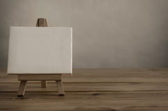 Blank Canvas and Easel on Wood Planking Royalty Free Stock Photo
