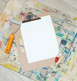 Blank canvas mockup with paints and brushes. On wooden table royalty free stock photo