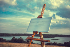 Blank canvas rests on a easel on lake landscape. Stock Photo