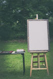 Blank canvas rests on a easel. Retro stylized Royalty Free Stock Image