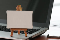 Blank canvas and wooden easel on laptop computer. As concept Stock Images