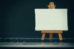 Blank canvas and wooden easel on laptop computer Royalty Free Stock Image