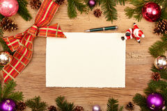 Blank card, ballpen, fir twigs and ribbon, on wood. En background Stock Photos