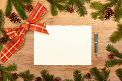 Blank card, ballpen, fir twigs and ribbon, on wood. En background Royalty Free Stock Photography