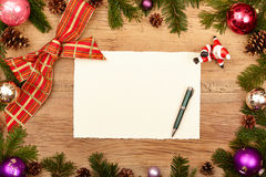 Blank card, ballpen, fir twigs and ribbon, on wood. En background Stock Image