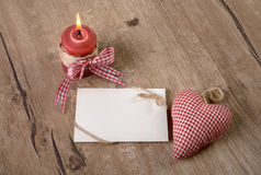 Blank card with burning candle and cotton heart on wood Royalty Free Stock Photos