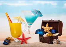 Blank card, cocktail, juice, starfish, presents in sand against sea. Royalty Free Stock Photos