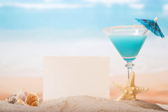 Blank card, cocktail, seashells and starfish in sand against sea. Stock Image