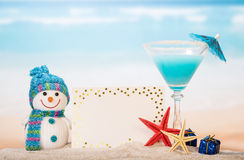 Blank card, cocktail,  snowman and gifts in  sand against sea. Royalty Free Stock Photos