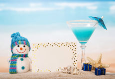 Blank card, cocktail, snowman, star in sand against sea. Royalty Free Stock Image
