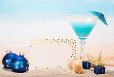 Blank card, cocktail, starfish, Christmas gifts in sand against  sea. Royalty Free Stock Photos