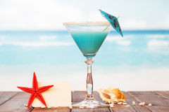 Blank card, cocktail, starfish and shell in  sand against  sea. Royalty Free Stock Photography