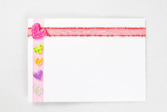 Blank card with colorful hearts over rose ribbon Royalty Free Stock Image