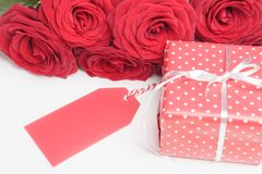 Tag, gift box and roses on white Royalty Free Stock Photos