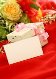 Blank card, gift and flowers on red background Royalty Free Stock Images