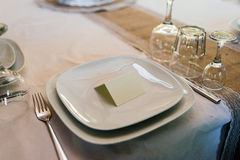 Blank card for guests on a white empty plate. On a dinner table Stock Photo