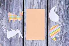 Blank card and paper animalistic silhouettes. Cut out paper birds and rabbits with empty paper card on rustic wooden background. Creative idea for easy Easter stock photography