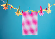Blank card pinned on clothesline. Copy space for wordings. Pinned with flower pins. Blue, orange background. High Royalty Free Stock Photo