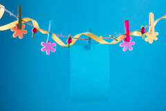 Blank card pinned on clothesline. Copy space for wordings. Pinned with flower pins. Blue, orange background. High Royalty Free Stock Photography