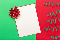 Blank card with red bow and streamer on colorful background Stock Photo