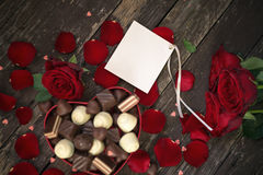 Blank card with red rose and chocolate pralines on a wooden back Royalty Free Stock Photos