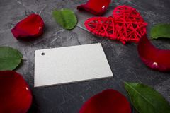 A blank card for a signature among the leaves of a rose and a red heart on a dark background. Valentine`s day or wedding. View from above Royalty Free Stock Photos