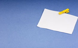Blank card with space for notes on the wooden clothespin colored paper on blue background Stock Image