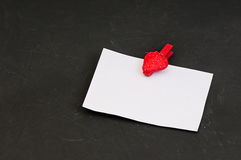 Blank card with space for records on clothespin in the form of strawberries on black stone background Stock Photos