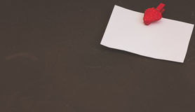 Blank card with space for records on clothespin in the form of strawberries on black stone background Royalty Free Stock Photography