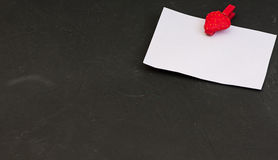 Blank card with space for records on clothespin in the form of strawberries on black stone background Stock Images