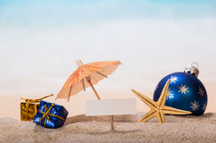 Blank Card, Starfish, Gifts, Christmas Ball In Sand Against Sea. Royalty Free Stock Photo