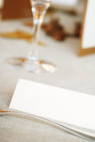Blank card on wedding table. A closeup view focusing on a blank card in the foreground with several other items on a wedding table in the background.  Narrow Royalty Free Stock Image