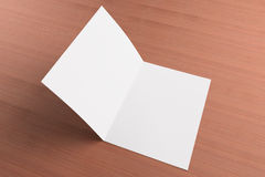 Blank card on wooden background. Blank opened card or flyer on wooden background, to replace message or image on cover Stock Photos