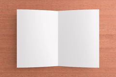 Blank card on wooden background. Blank opened card or flyer on wooden background, to replace message or image on cover Stock Image