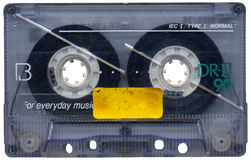 Blank Cassette Tape. Dirty, scratched and grungy retro cassette tape with a blank label Stock Image