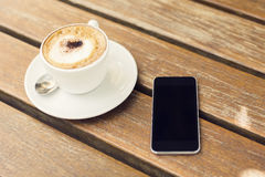 Blank cell phone and cup of coffee Stock Photos