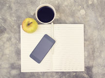 Blank cell phone, diary and cup of coffee. Close up Royalty Free Stock Image