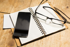 Blank cell phone diary and glasses Stock Photos