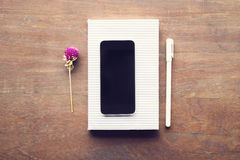 Blank cell phone, diary and pen on a wooden table Stock Photography