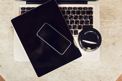Blank cell phone, digital tablet, laptop and coffee Royalty Free Stock Images