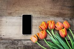 Blank Cell Phone and Flowers. Overhead shot a blank cell phone with a bouquet of orange and yellow tulips over a wood table. Flat lay top view style stock photography