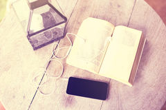 Blank cell phone, headphones and a book on the table. Close up stock photography