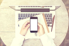 Blank cell phone screen with diary and laptop on wooden table, m. Ock up royalty free stock images