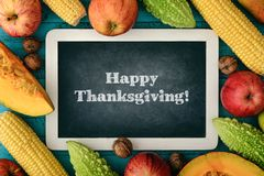 Thanksgiving day concept. Blank chalk board with apples, pears, pumpkin, nuts and bitter melon on wooden background, top view Stock Images