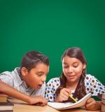 Blank Chalk Board Behind Hispanic Boy and Girl Having Fun Studying royalty free stock images