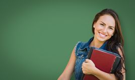 Blank Chalk Board Behind Mixed Race Young Girl Student Holding Books Royalty Free Stock Photography