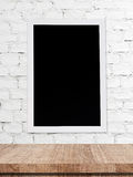 Blank chalk board over wooden table and white brick wall backgro Stock Photography